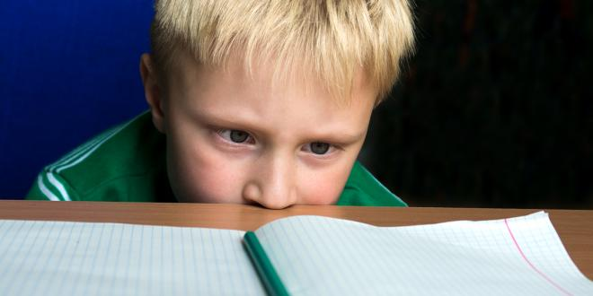 A child staring helplessly at his blank schoolwork